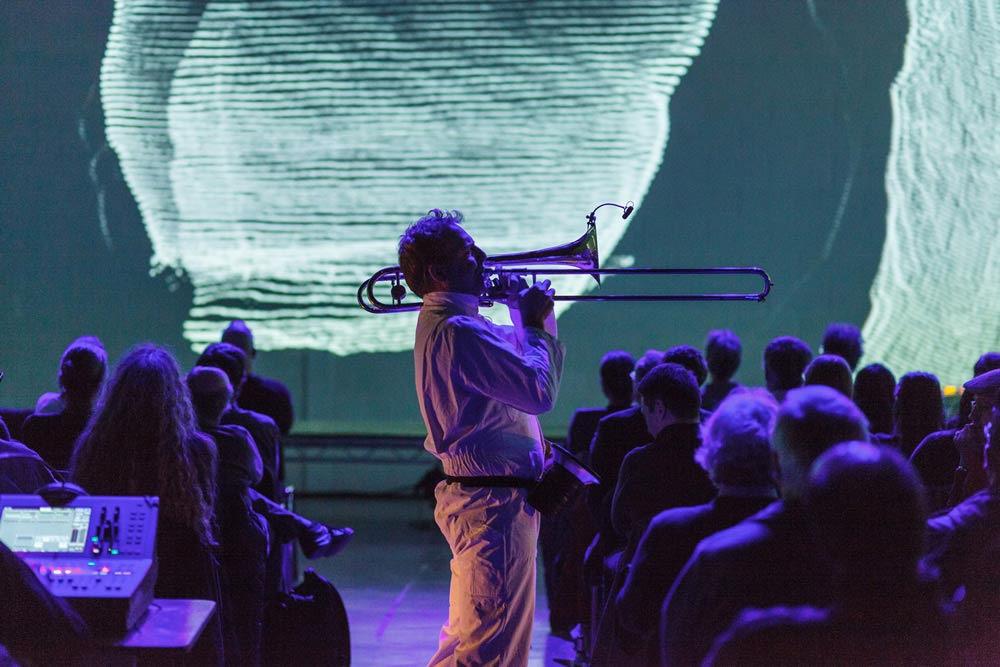 Silhouette of trombone player with DPA microphone - Oktophonie performance at Huddersfield Contemporary Music Festival (photo by Graham Hardy)